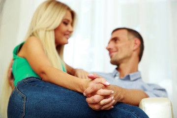 Young couple sitting on the sofa at home. Focus on hands