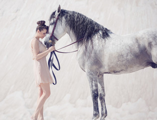 Beautiful young woman hugging the horse