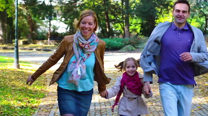 Happy young parents with daughter running through the park