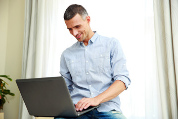 Happy man using laptop at home
