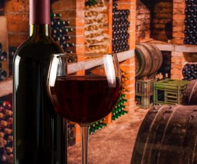 red wine glass near bottle on old wine cellar background