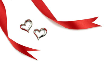 Red ribbons and silver heart shape on white background