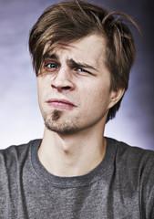 Studio portrait of a suspicious young man