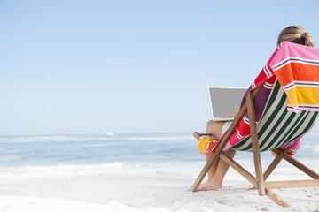 Woman sitting on beach in deck chair using laptop