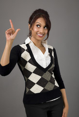 Indian businesswoman smiling and pointing upwards