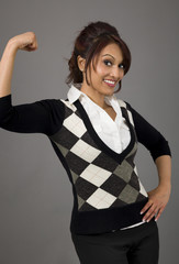Indian businesswoman flexing biceps and smiling