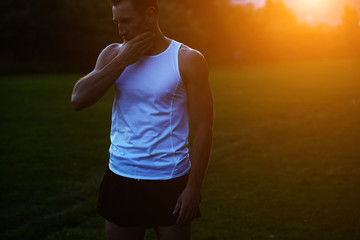 Beautiful runner with muscular body resting in the park