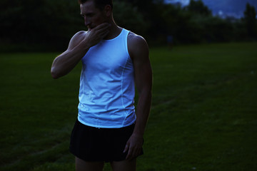 Athletic man with muscular body resting after intensive jog