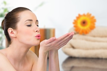 Composite image of beautiful brunette blowing over hands