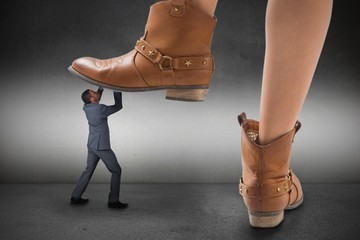Composite image of cowboy boots stepping on businessman