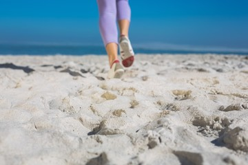 Sporty womans feet jogging on the sand