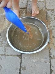 Kind spielt mit Sand und Wasser