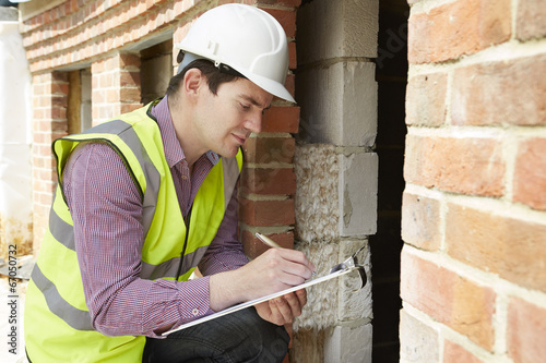 Architect Checking Insulation During House Construction - 67050732