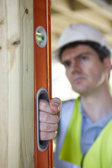 Builder Checking Work With Spirit Level
