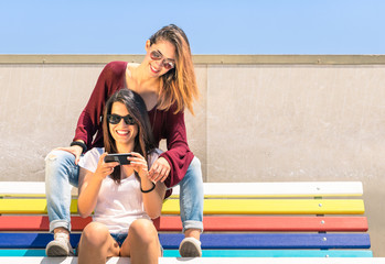 Best friends enjoying time together outdoors with smartphone