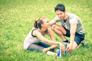Young happy couple sport training stretching in the park