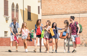Group of happy best friends with shopping bags in the city