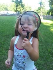 bambina che guarda con lente d'ingrandimento