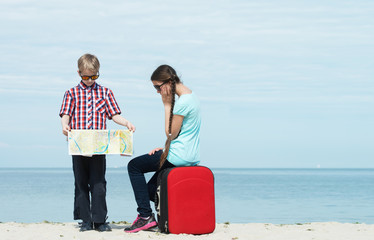 Children going for vacation with a luggage and a map