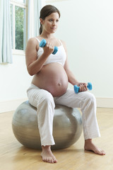 Pregnant Woman Sitting On Exercise Ball With Weights