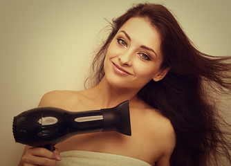 Happy smiling woman drying long hair and looking in camera