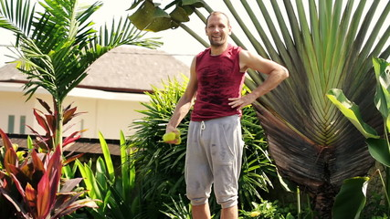 Portrait of happy sporty man with dumbbels in the garden