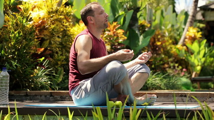 Young handsome man meditating in the garden