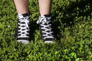 Girl legs with sneakers on fresh green grass background