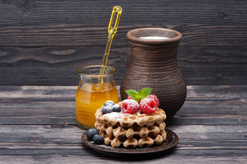 Waffles with berries, honey and milk. Breakfast