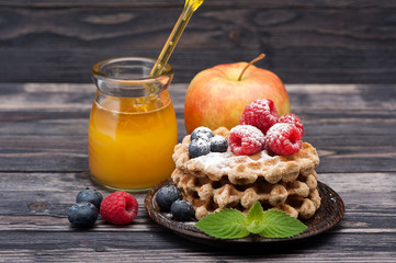 Waffles with raspberries, blueberries, fruit and honey.