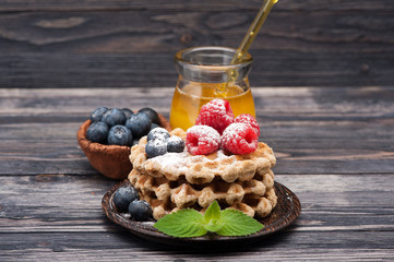 Waffles with blueberries, raspberries and honey. Breakfast