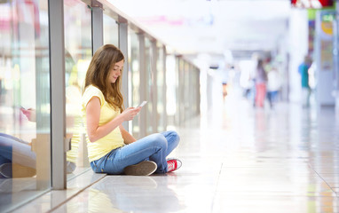 Girl with smartphone in shopping mall