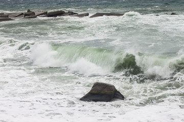 Sea waves rolling on stones