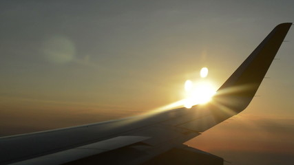 Airplane wing in flight at sunrise