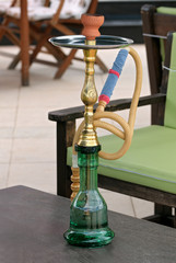 Green and gold hookah on the table of an outdoor cafe