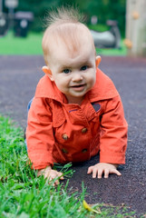 cute baby in red trench crawling on a playground outdoor