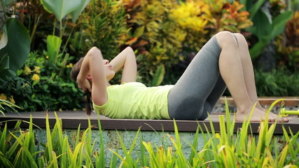 Young attractive woman doing sit-ups exercise in garden