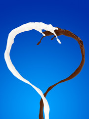 Heart of chocolate and milk splash on blue background