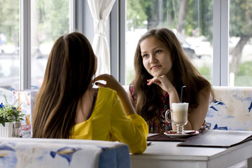 Conversation of girls behind a cup of coffee