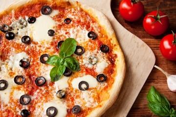 Pizza Margherita mit Oliven und Basilikum