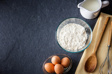 Baking ingredients - flour, milk, eggs with a whisk, wooden spoo