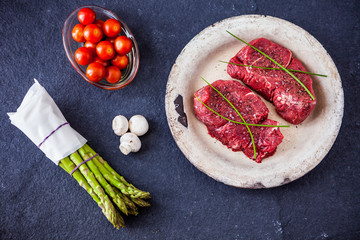 Two raw filet steaks with green asparagus, mushrooms, cherry tom