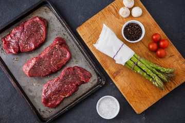 Three raw filet steaks with green asparagus, mushrooms, cherry t