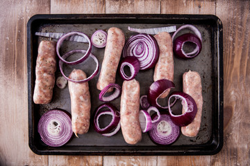 Baking tray with six raw pork and apple sausages covered