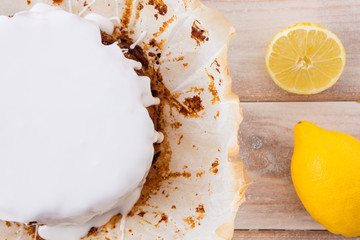 Freshly baked lemon cake with white icing and fresh lemons