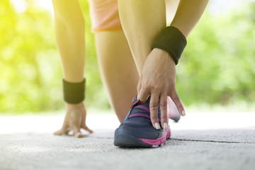 woman preparing to run on park pathway