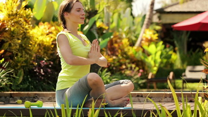 Young attractive woman meditating in the garden
