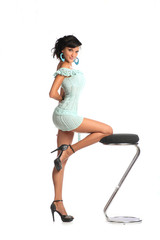 Woman with fashion hairstyle poses at studio on bar stool