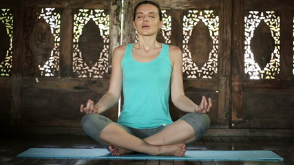 Young beautiful woman meditating at home