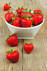 Bowl full of juicy strawberries on a wood background